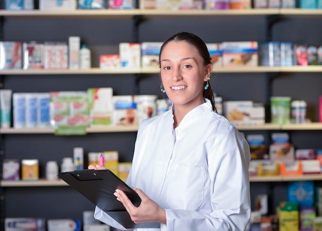 Красивая фармацевт, используя блокнот в аптеке