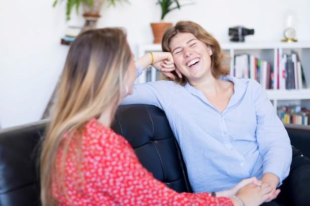 Двое друзей разговаривают и смеются на диване в гостиной дома