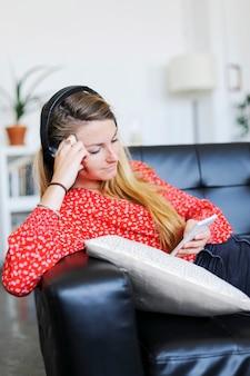 幸せな女がソファーに座っていたスマートフォンを使用してヘッドフォンを着て音楽を聴く