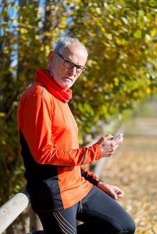 ジョギングの後彼のスマートフォンを見ているシニアランナー男