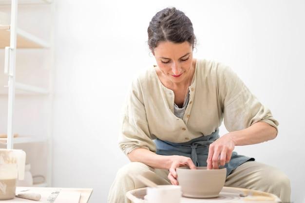 女性の手は陶器のホイールに粘土ポットになります