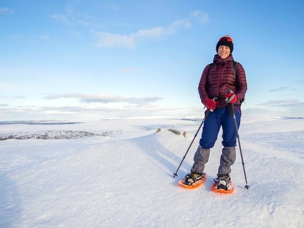 Красивая, молодая женщина на снегоступах и наслаждается великолепной зимней погодой с обилием снега