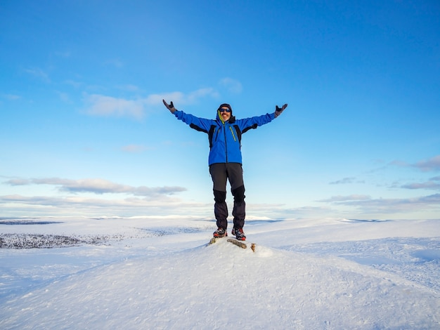 彼の手を上にして雪に覆われた山の頂上にいる男