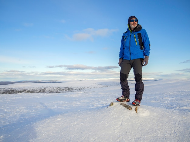 Одинокий альпинист отдыхает на снежной горе высоко над облаками над солнцем