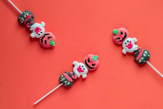 色付きの背景に交互のパターンで配置されたハロウィーンキャンディー
