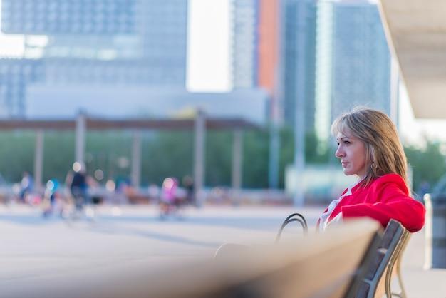 街のベンチに座っている赤いジャケットを着て金髪の女性の側面図