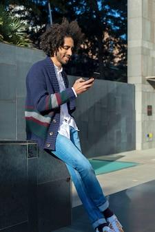 晴れた日に屋外のベンチに座って笑顔で彼のスマートフォンを使用して若いハンサムなアフリカ人