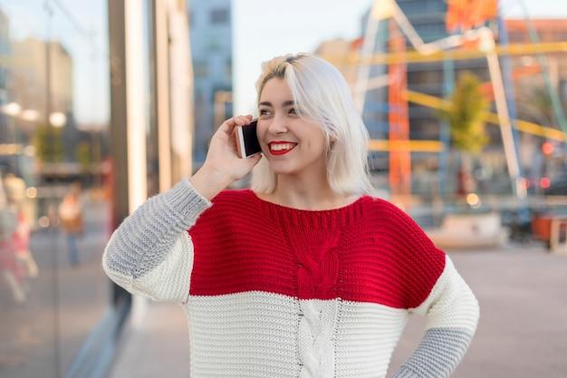 スマートフォン屋外で話している陽気な若い女性の肖像画。