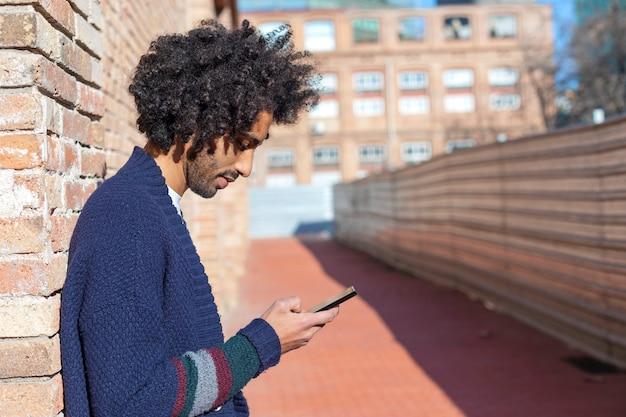 晴れた日に屋外のレンガの壁にもたれながら笑顔で彼のスマートフォンを使用して若いハンサムなアフリカ人