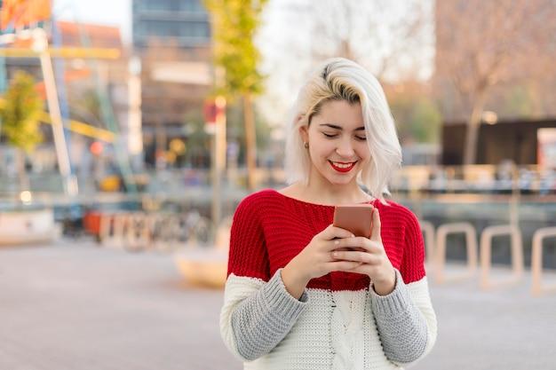 美しい女性が買い物をしながら彼女の電話でメッセージを書きます。