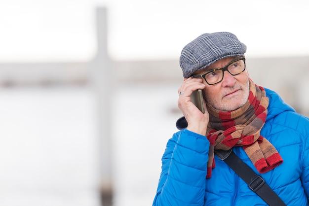年配の男性が通りで携帯電話で話しています。