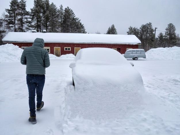 雪に覆われた車の横を歩く一人の男