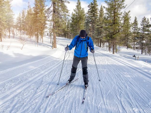 フィンランドのトレイルでクロスカントリースキーをする男性の正面図