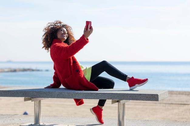 屋外で携帯電話を使用しながら、ビーチのベンチに座っている若い美しい巻き毛のアフリカ系アメリカ人女性の側面図