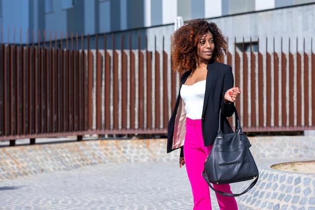 晴れた日に通りに立っている間エレガントな服とハンドバッグを着ている若い美しい巻き毛の女性の正面図