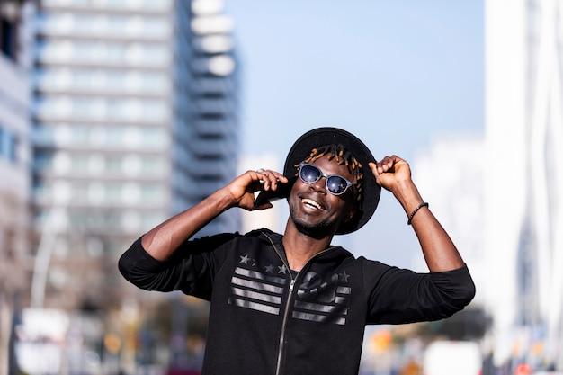 Вид спереди чернокожего человека с солнечными очками и шляпой стоя против городского пейзажа на улице пока использующ мобильный телефон в солнечном дне.