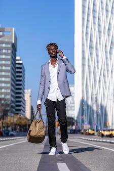 Вид спереди молодого человека чёрного африканца, идущего по улице в элегантной куртке и держащего сумку при использовании телефона в солнечный день