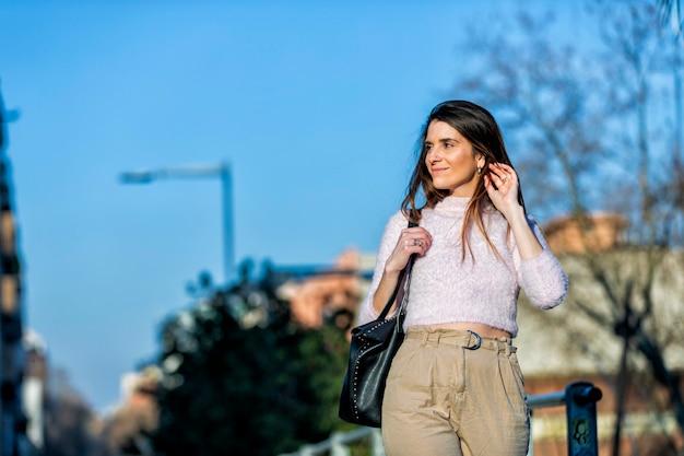 Вид спереди улыбающиеся волосы красивой молодой женщины трогательно и стоя на улице, глядя в солнечный день