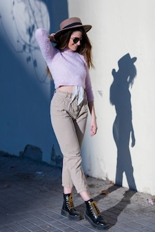 サングラスと帽子が晴れた日にポーズをしながら通りに立っている身に着けている美しいトレンディな若い女性の正面図