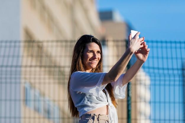 Вид спереди красивой модной молодой женщины, носить повседневную одежду, стоя на улице, принимая селфи, улыбаясь в солнечный день