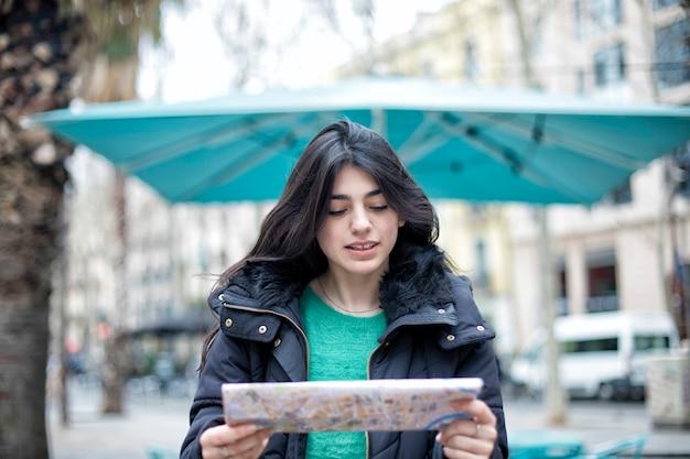 ロケーションマップ上の方向を検索する幸せな美しいカジュアルな女性旅行者の肖像
