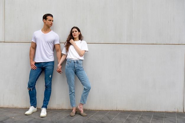 明るい日にカジュアルな服を着て手を繋いでいる壁にもたれて幸せなカップル