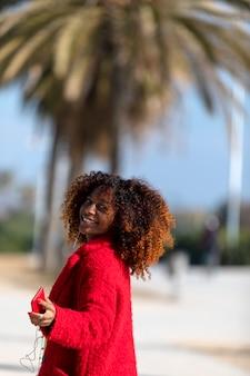 笑みを浮かべて、晴れた日に離れて見ながら屋外に立っている若い笑顔巻き毛女性