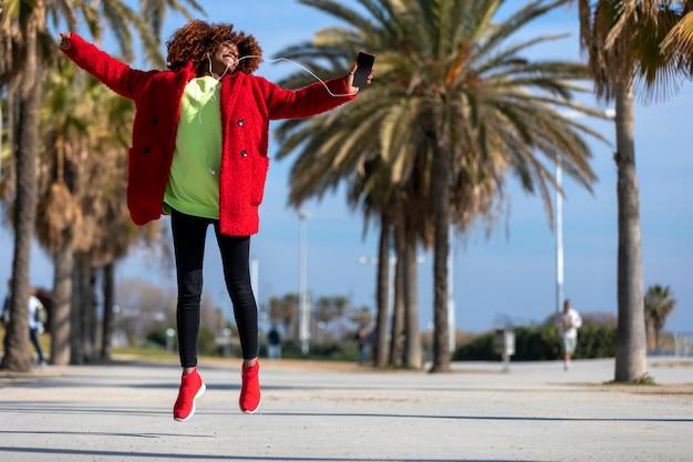 若い美しい巻き毛のアフリカ系アメリカ人女性ジャンプとダンス音楽を聴きながら、屋外で笑顔