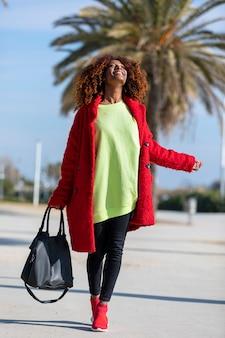 笑みを浮かべて、晴れた日に都市の道に立っている間よそ見若い美しい巻き毛のアフロ女性