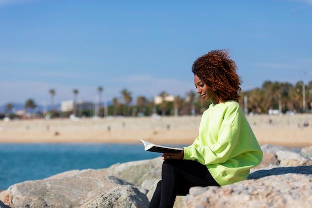 Молодая вьющаяся женщина сидит на волнорезе, держит книгу, улыбается и смотрит на улицу