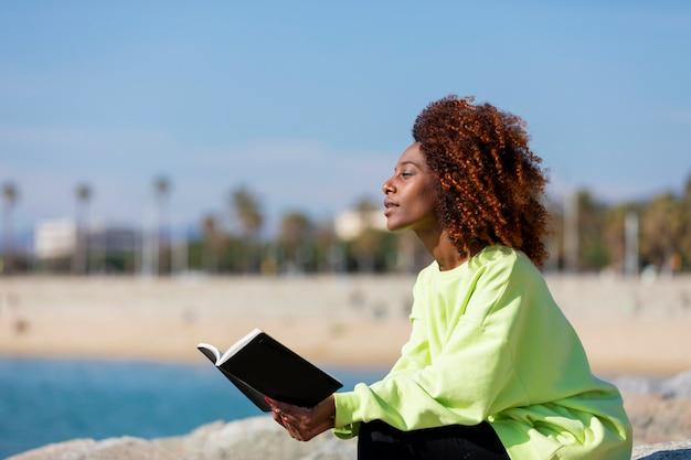 笑みを浮かべて、離れて屋外を見ながら本を保持している防波堤の上に座って若い巻き毛の女性