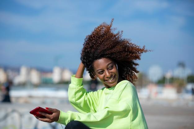 防波堤に座っている若い巻き毛のアフロ女性岩を楽しんで、晴れた日に携帯電話を使用して音楽を聴きながら笑顔