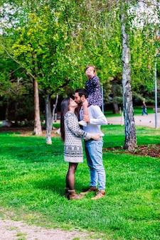 Семейные мама, папа и дочка сидят у папы на плечах, а родители целуются в парке при дневном свете