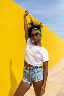 髪に触れながら黄色の壁に立っているサングラスを持つ若いアフリカ人女性。