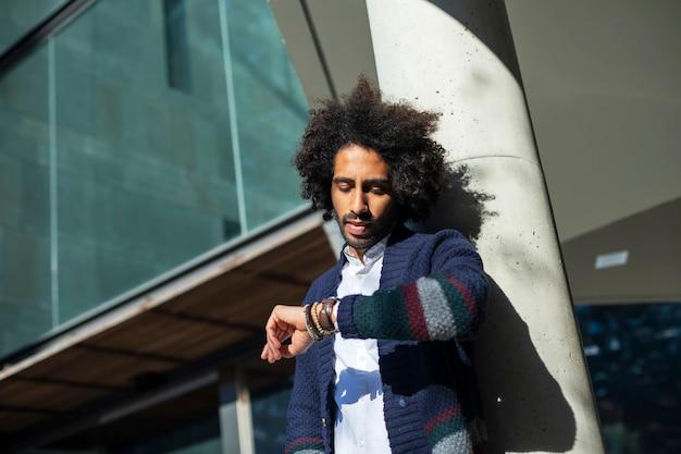 Молодой красавец с афро волосами проверка времени на наручных часах