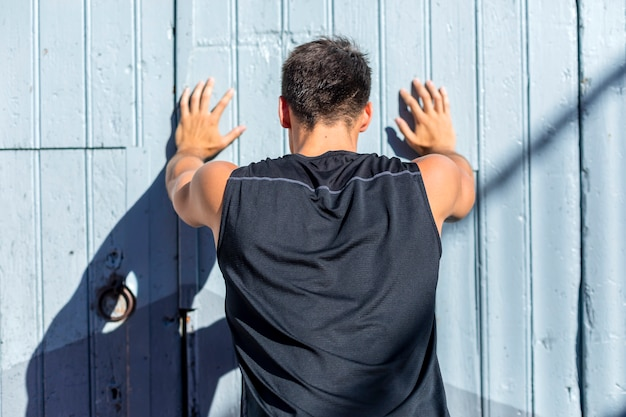 Молодой человек растягивается на фоне голубой стены после тренировки