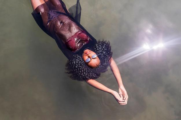 Красивая молодая афро-американская женщина плавая в бассейн воды