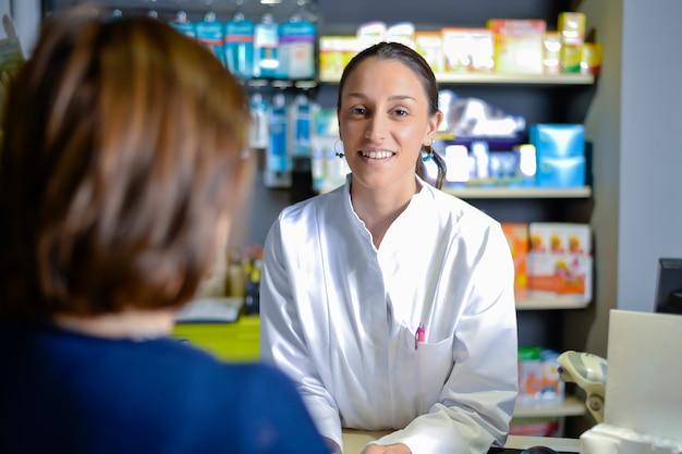 Улыбающийся привлекательный молодой рыжий фармацевт, вручающий прописанные лекарства пожилой пациентке, рассматривает клиентов через плечо фармацевта