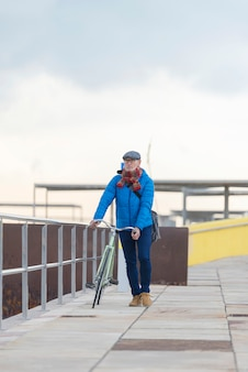 通りで彼の自転車を歩いて肖像画年配の男性