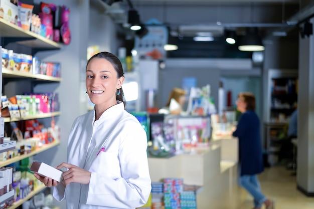 Молодая усмехаясь женщина аптекаря работая в аптекаре