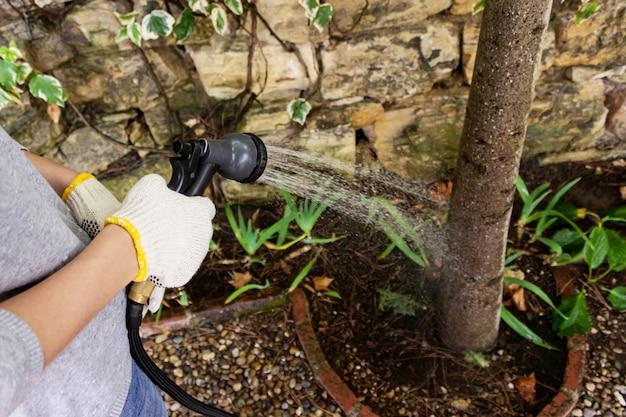 Портрет молодой женщины садовника полива сада