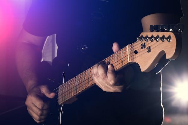 男は黒の背景でエレキギターを持っています。