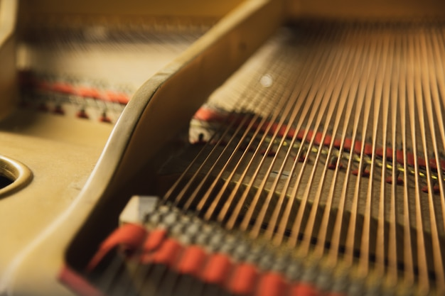 銅のひもが付いている古典的なグランドピアノの楽器の内側。