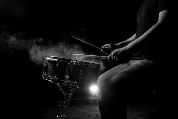 男はスネアドラムを演奏しています。