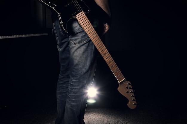 Мужчина в джинсах держит электрогитару на черном фоне
