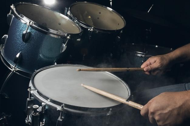 男は暗い光の背景に設定されたドラムを演奏しています。