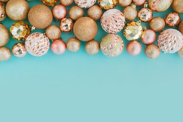 Рама с золотой елочные шары на бледно-голубом фоне с блестками.