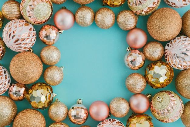 Рама с блестками и золотые шары елки на бледно-голубом фоне. праздничная концепция, вид сверху.