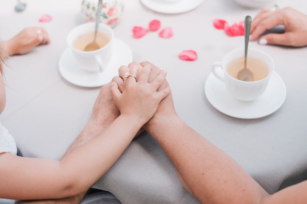 一緒に保持しているテーブルの上の親と子の手。