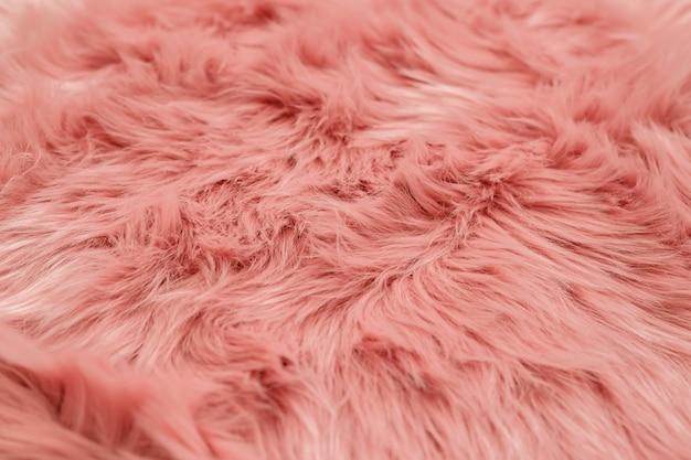 ピンクの毛皮の背景。ピンクのシープスキンの背景色と質感。